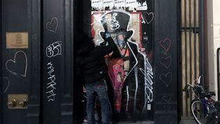 """L'artiste """"Saynosleep"""" peignant une porte dans la ville de New York (THOMAS URBAIN / AFP)"""