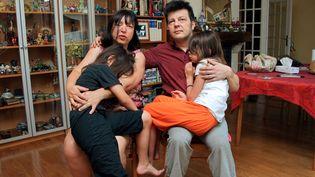 Sylvie et Dominique Mennesson posent avecleursjumelles nées en 2000 d'une mère porteuse, le 2 juillet 2009 à Maisons-Alfort (Val-de-Marne). (PIERRE VERDY / AFP)