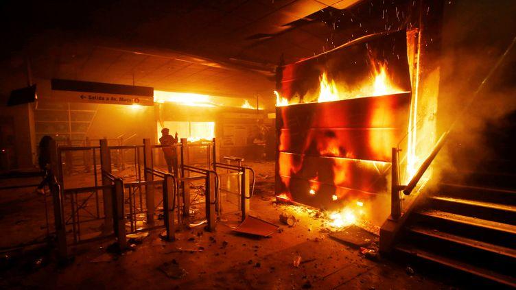 Une billetterie d'une station de métro incendiée lors d'affrontements à Santiago (Chili), vendredi 18 octobre 2019. (STRINGER . / X80002)
