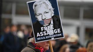 """Un manifestant brandissant une pancarte """"Libérez Assange - Pas d'extradition aux USA"""", le 24 février 2020 lors d'un rassemblement de soutien devant la prison où se trouve le fondateur de Wikileaks. (DANIEL LEAL-OLIVAS / AFP)"""