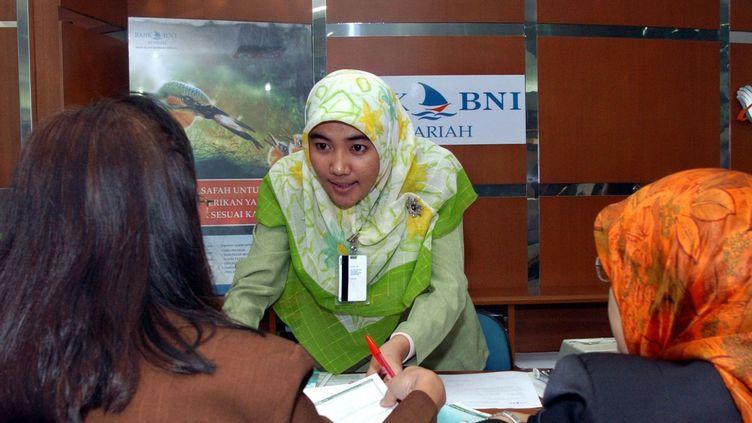 Une employée indonésienne de la division islamique de la Bank Negara Indonesia avec deux clientes (2003). (AFP PHOTO / ADEK BERRY)