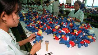 Des salariées d'une usine de jouets de Bangkok (Thaïlande) mettent la dernière mains aux peluches Footix, le 9 juin 1998. (PORNCHAI KITTIWONGSAKUL / AFP)