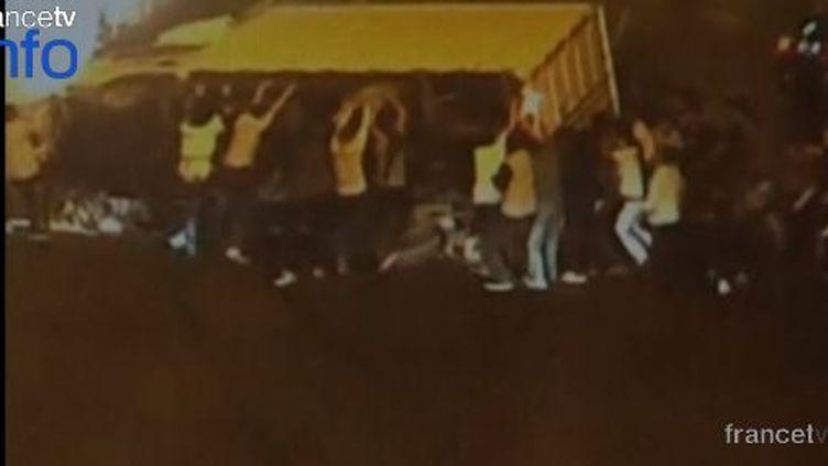 Une capture d'écran d'une vidéo de surveillance montre des passants qui soulèvent un camion afin de libérer un conducteur de deux-roues, coincé sous le véhicule, le 1er avril 2015, à Hangzhou (Chine). (CCTV / REUTERS )