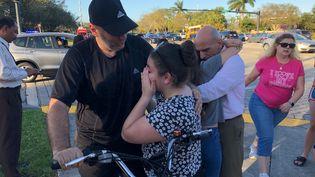 Des personnes se réconfortent après une fusillade dans un lycée de Parkland (Floride), le 14 février 2018. (MICHELE EVE SANDBERG / AFP)