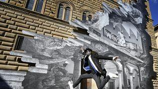 """L'artiste français JR devant sa dernière oeuvre, """"La Ferita"""" (la blessure), à Florence, le 19 mars 2021 (ALBERTO PIZZOLI / AFP)"""
