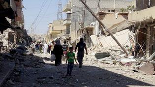 Des Syriens dans les décombres après un nouveau bombardement sur Alep (Syrie), le 27 juillet 2016. (MAMUN EBU OMER / ANADOLU AGENCY / AFP)