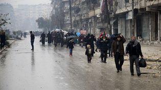Des habitants quittent une zone rebelle d'Alep, en Syrie, le13 décembre 2016. (KARAM AL-MASRI / AFP)