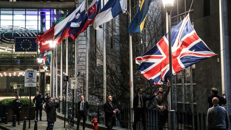 Le drapeau britannique est retiré par des employés, devant le Parlement européen à Bruxelles (Belgique), le 31 janvier 2020. (ARIS OIKONOMOU / AFP)