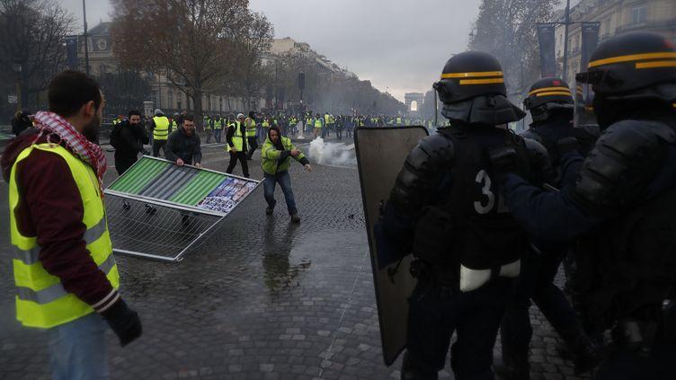 Des manifestants vêtus de gilets jaunes font face aux forces de l'ordre samedi 24 novembresur les Champs-Élysées, à Paris. (CHRISTOPHE PETIT TESSON / EPA)