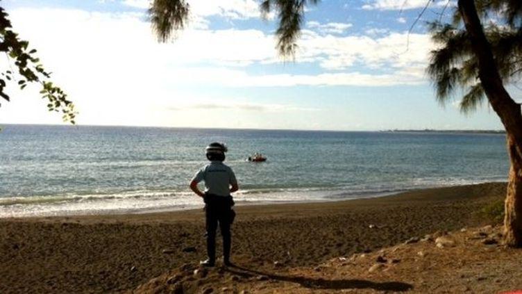 Un gendarme observe la plage de l'île de La Réunion où une adolescente est morte tuée par un requin, le 15 juillet 2013. (H.DEBEUX / REUNION 1ERE)
