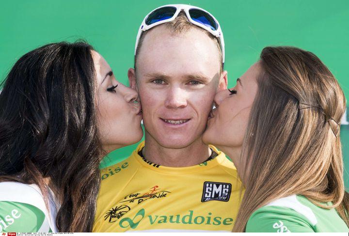 Christopher Froome, entouré par deux hôtesses, sur le podium du Tour de Suisse, le 25 avril 2013. (JEAN-CHRISTOPHE BOTT / AP / SIPA)