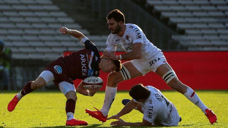 Matthieu Jalibert (UBB), auteur de 21 points lors de la rencontre, est taclé par le Toulonnais Charles Ollivon. (ROMAIN PERROCHEAU / AFP)