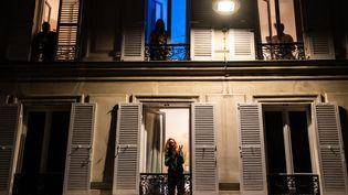 Des Parisiens à leur fenêtre le 18 mars à 20 heures applaudissement pour rendre hommage aux soignantsengagés dans la lutte contre le coronavirus. (MARTIN BUREAU / AFP)