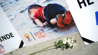 A Ankara, en Turquie,des fleurs ont été déposées le 3 septembre devant une affiche du mouvement de jeunesse de l'AKP (le parti au pouvoir) représentant Aylan al-Kurdi, l'enfant syrien de 3 ans retrouvé mort sur une plage de Bodrum, dont la photo a fait le tour du monde. (CITIZENSIDE/OSMANCAN G?DOGAN / CITIZENSIDE.COM)