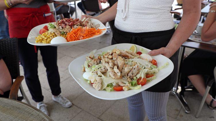 Une serveuse avec deux assiettes pleines. Photo d'illustration. (THIERRY GACHON / MAXPPP)