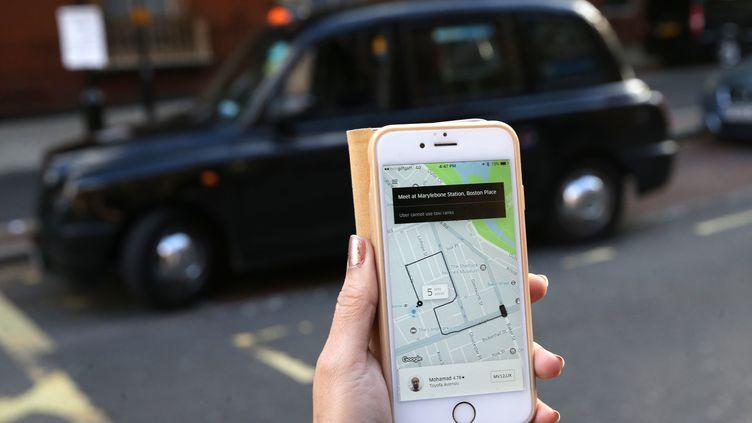 Une utilisatrice commande un Uber à Londres (Royaume-Uni), le 22 septembre 2017. (DANIEL LEAL-OLIVAS / AFP)