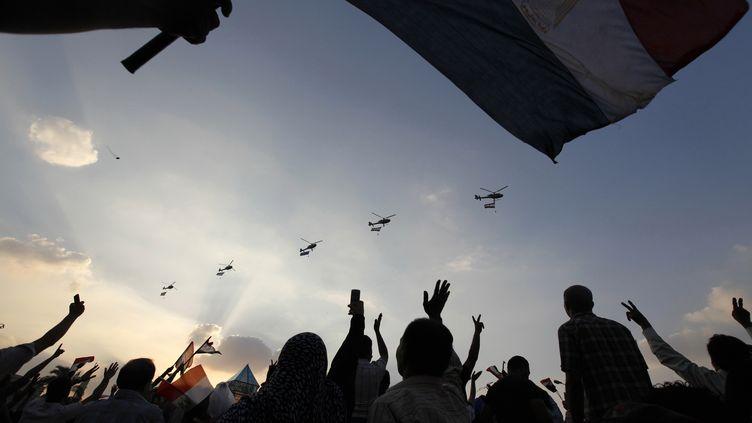 Des opposants au président Mohamed Morsi défilent sur la place Tahrir, tandis que des hélicoptères de l'armée suvolent le ciel du Caire (Egypte), lundi 1er juillet. (MOHAMED ABD EL GHANY / REUTERS)