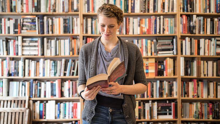 Jeune femme lisant dans une librairie  (Luis Alvarez / Getty Images)