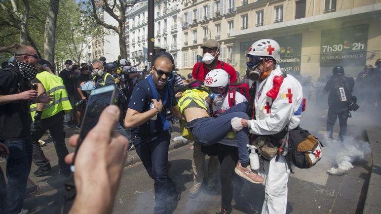 """Des """"street medics"""" venant en aide à un manifestant blessé dans les rues de Paris, le 20 avril 2019. (JEREMIAS GONZALEZ / AFP)"""