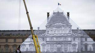 La pyramide du Louvre, à Paris, recouverte d'une photographie du musée par l'artiste JR, le 24 mai 2016. (JOEL SAGET / AFP)
