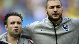"""Karim Benzema et Mathieu Valbuena bras dessus-bras dessous en équipe de France (ici le 30 juin 2014 au Mondial au Brésil),c'était avant le scandale de la """"sextape"""". (FRANCK FIFE / AFP)"""