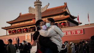 Un homme porte une fille dans ses bras, les deux avec un masque pour se protéger des virus, à Pekin (Chine), le 24 janvier 2020. (NICOLAS ASFOURI / AFP)