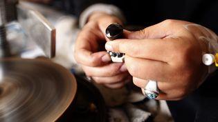 La jeune artisane Safaa al-Faqih fait briller les pierres sur la meuleuse, 2018  (Mohammed HUWAIS / AFP)