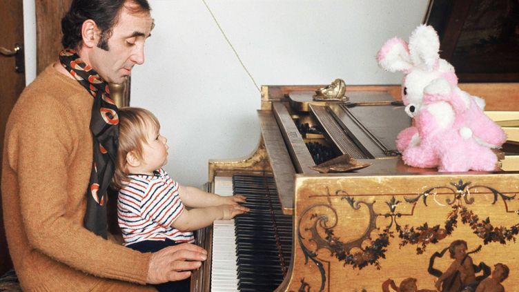Charles Aznavour au piano avec sa petite Katia en 1971 à Montfort-L'Amaury.  (Ginies/SIPA)