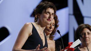 """La cinéaste italienne Alice Rohrwacher, une des deux femmes en compétition officielle, lors de son discours de remerciement après avoir gagné le Grand Prix du jury pour """"Les Merveilles"""" en 2014  (VALERY HACHE / AFP)"""