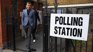 Des électeurs britanniques sortent d'un bureau de vote, le 8 juin 2017, à Londres (Royaume-Uni), aux premières heures des élections législatives anticipées. (JUSTIN TALLIS / AFP)