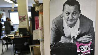 Une photo de Coluche, fondateur desRestos du Cœur, au centre d'Asnières-sur-Seine (24 novembre 2020). (STEPHANE DE SAKUTIN / AFP)
