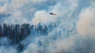 Un hélicoptère déverse de l'eau sur les incendies en Australie, le 29 décembre 2019. (HANDOUT / DEPARTMENT OF ENVIRONMENT, LAND,)