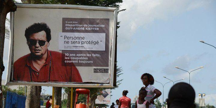 Dans les rues d'Abidjan (Côte d'Ivoire), le 16 avril 2014, un portrait du journaliste franco-canadien Guy André-Kieffer disparu dix ans plus tôt. L'affiche est issue d'une campagne initiée par l'ONG française de défense de la liberté de la presse, Reporters sans frontières (RSF), pour marquer le dixième anniversaire de sa disparition en Côte d'Ivoire.  (AFP PHOTO / ISSOUF SANOGO)