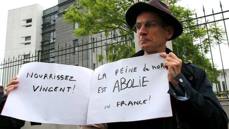Un membre du comité de soutien du tétraplégique français Vincent Lambert, pancarte à la main, dimanche 19 mai lors d'une manifestation devant le CHU de Reims (FRANCOIS NASCIMBENI / AFP)