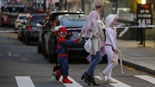 Une mère de famille avec ses deux enfants passent devant un cordon de sécurité, près du lieu où a été arrêté le terroriste, le 31 octobre 2017 à New York. (KENA BETANCUR / GETTY IMAGES NORTH AMERICA / AFP)