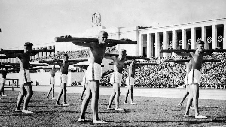 Des gymnastes allemands paradent dans un stade en 1938  (STAFF / AFP)
