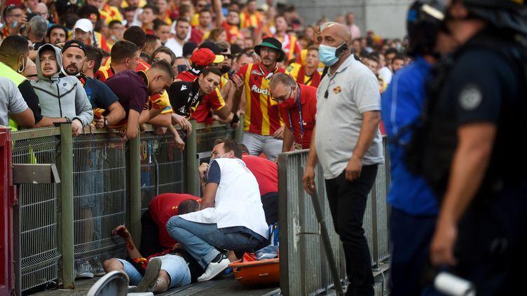 Le staff medicals'occupant d'un supporter blessé lors du match de Ligue 1 Lens-Lille le 18 septembre 2021 au stade Bollaert-Delelis. (FRANCOIS LO PRESTI / AFP)