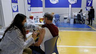 Un homme se fait vacciner avec le vaccin Pfizer-BioNtech contre le Covid-19, dans le parking d'un centre commercial, à Tel Aviv (Israël), le 26 janvier 2021. (JACK GUEZ / AFP)