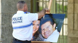 Un policier décrochant une photo de Jean-Baptiste Salvaing et Jessica Schneider, tués dans leur résidence à Magnanville, après un hommage organisé à Pezenas le 20 juin 2016. (SYLVAIN THOMAS / AFP)
