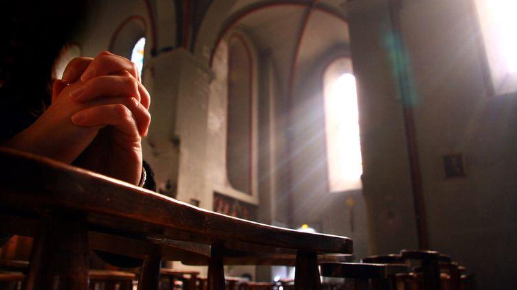 Lors de tête à tête, le prêtre proposait à ses victimes d'effectuer des prières qui se terminaient pardes frottements sexuels. Photo d'illustration d'une personne qui prie à l'intérieur d'une église. (MAXPPP)
