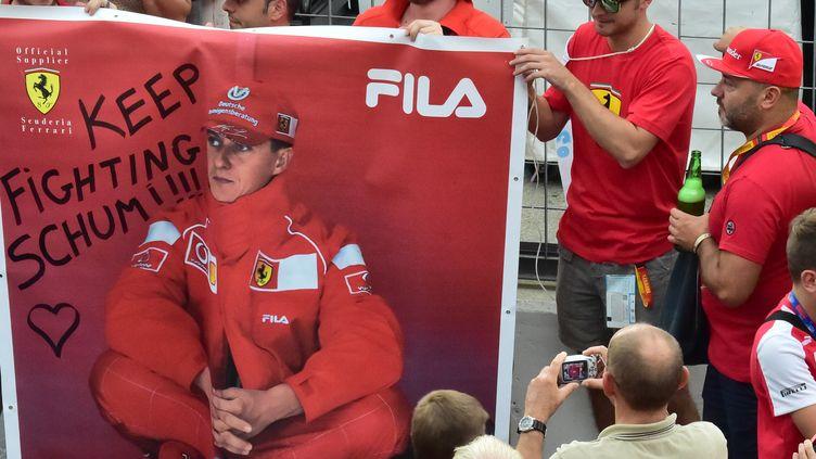 Des supporters de Ferrari brandissent une banderole de soutien à Michael Schumacher.  (GIUSEPPE CACACE / AFP)