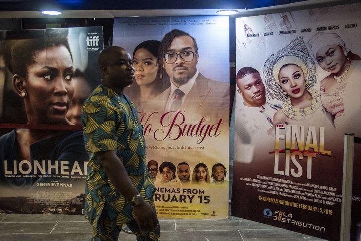 """Un homme passe devant les affiches de films """"Nollywood"""" projetés dans un cinéma à Lagos, au Nigeria, le 19 février 2019. (CRISTINA ALDEHUELA / AFP)"""