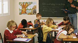 Six élèves et un professeur en classe. (SYLVA VILLEROT / PHOTONONSTOP / AFP)