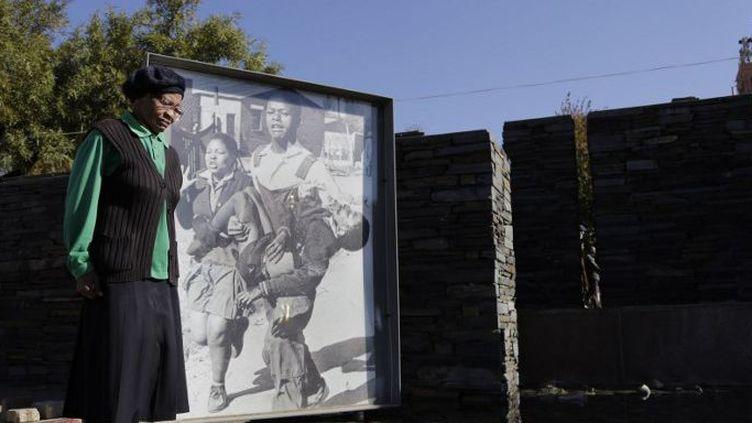 Une femme se tient en silence devant le mémorial sur lequel on peut voir une photo montrant Hector Pieterson, tué le 16 juin 1976 à Soweto. (CORNELL TUKIRI / ANADOLU AGENCY)