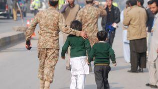 Un soldat escorte des élèves de l'établissement attaqué par les talibans, le 16 décembre 2014, à Peshawar (Pakistan). (KHURAM PARVEZ / REUTERS)