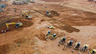 Photographie aérienne de pelleteuses et de camions sur le site de construction du nouveau hôpital, à Wuhan (Chine), le 27 janvier 2020. (HECTOR RETAMAL / AFP)