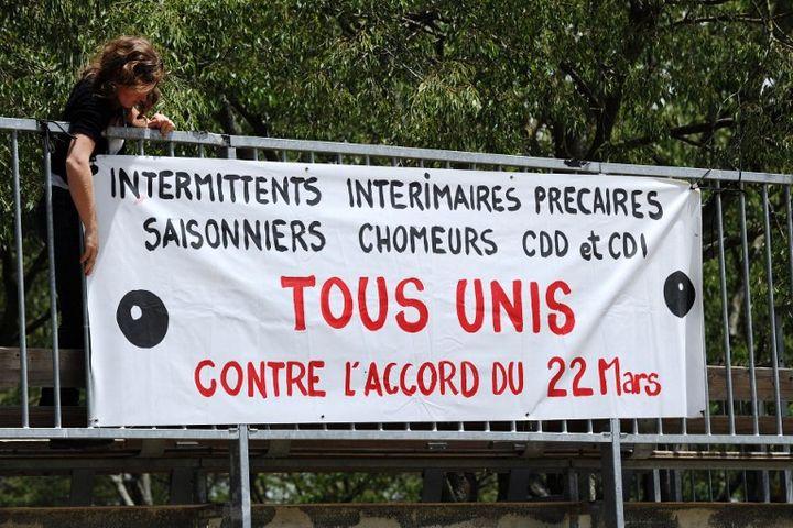 Une femme pose une bannière à Montpellier le 6 juin 2014 pour la reconduction de la grève des intermittents  (SYLVAIN THOMAS / AFP)