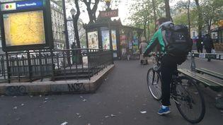 Kevin, livreur à vélo pour Take Eat Easy, patiente entre deux courses à la station de métro Bonne Nouvelle, à Paris. (JULIETTE DUCLOS / FRANCETV INFO)