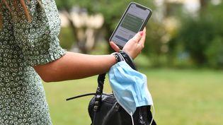 Une femme tenant son smartphone à la main et son masque sanitaire au poignet. Photo d'illustration. (FRANKHOERMANN/SVEN SIMON / SVEN SIMON)