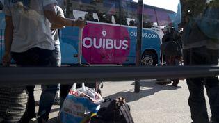 Des passagers attendent de monter dans un car Ouibus à Paris. (AFP)